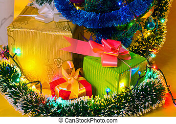 Ecologic Christmas tree made from gift boxes and rustic Christmas decorations on wooden background with Merry Christmas