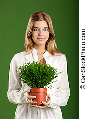 Portrait of a beautiful young woman holding a plant on her hands, isolated on a green background