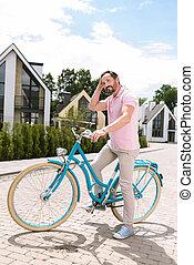 Joyful positive man standing with his bike