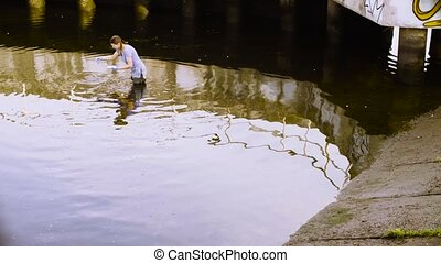 Ecologist getting samples of plants in the city river -...