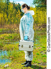 ecologist in overalls on the lake with equipment for taking water samples