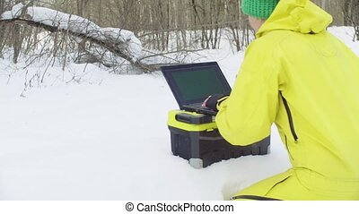 Ecologist in sportswear working on the laptop in winter...