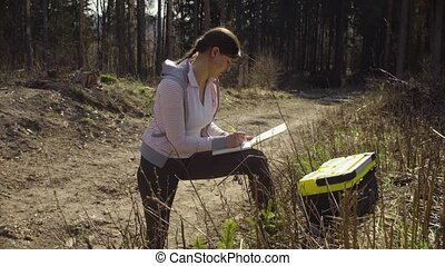 Ecologist in the forest marking place on the map. Save the...
