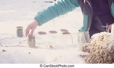 Ecologist prepares glass jars for samples and marks them -...