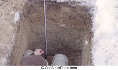 Ecologist probes layers of soil - Ecologist sitting in the...