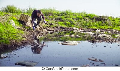 Ecologist taking samples of the water. - Woman scientist...