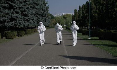 Ecologists team wearing hazmat suits in action running in the park concept of ecology and healthy life