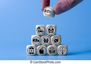 Ecology concept with icons on wooden cubes, blue background.