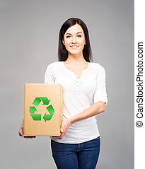 Ecology, environment, and a planet saving concept. Girl holding paper box with recycle symbol on it.
