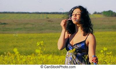 Ecology. Happy woman is blowing bubbles in a field of Raps.