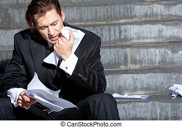 Businessman sitting on the stairs of building and looking at document