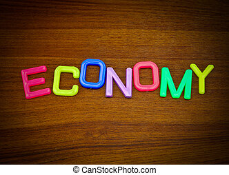 Economy in colorful toy letters on wood background