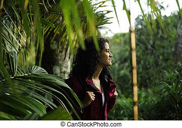 ecotourism: female hiker exploring wilderness of rainforest...
