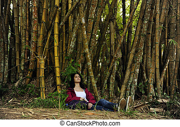 ecotourism: female hiker relaxing in the shadow of bamboo -...