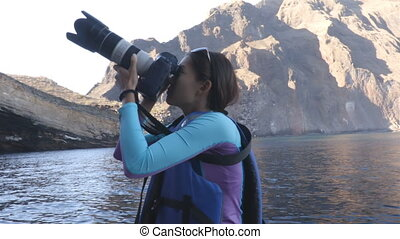 Ecotourism on Galapagos - tourist photographer taking photos of Galapagos wildlife in sailing in small zodiac dinghy boar by Punta Vicente Roca, Isabela, Galapagos Islands, Ecuador.