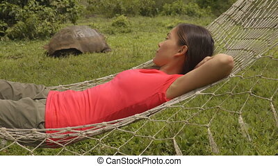 Ecotourism Travel adventure on Galapagos Islands, - tourist woman relaxing in hammock by Giant Tortoise Santa Cruz Island in Galapagos Islands.