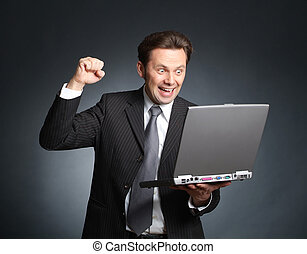 Ecstatic and enthusiastic businessman with laptop - good...