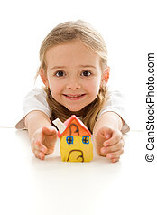 Ecstatic little girl with her clay house grimacing happily -...