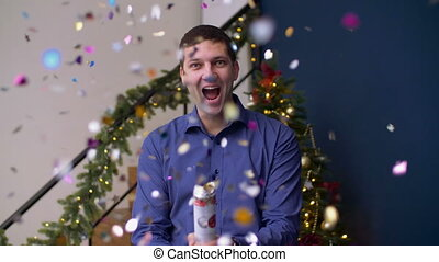 Ecstatic man exploding christmas confetti cracker - Portrait...