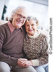 Ecstatic seniors - Laughing senior couple in sweaters...
