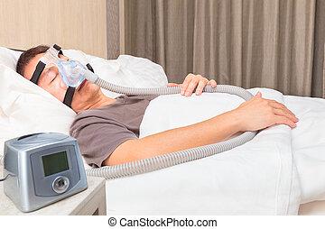 edad media, hombre asiático, sueño, en cama, llevando, cpap, máscara, de conexión, a, manguera de aire, y, cpap, máquina, dispositivo, para, gente, con, sueño, apnea