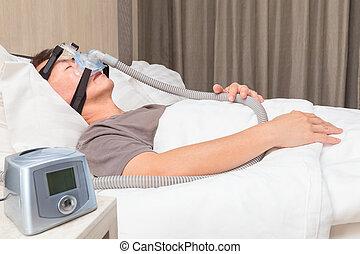 edad media, hombre asiático, sueño, en, el suyo, cama, llevando, cpap, máscara, de conexión, a, manguera de aire, y, cpap, máquina