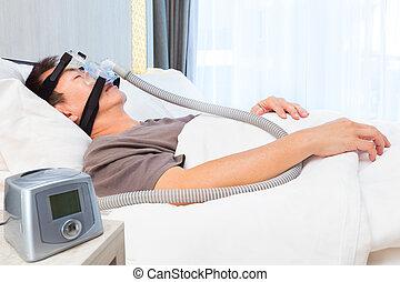 edad media, hombre asiático, sueño, llevando, cpap, máscara, de conexión, a, manguera de aire, y, máquina