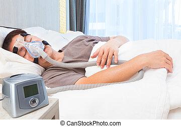 edad media, hombre asiático, sueño, llevando, cpap, máscara, de conexión, a, manguera de aire, y, machine`