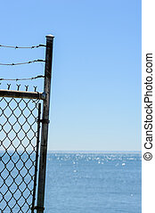 Edge of fence and barb wire against sky and water.