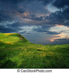 meadow and majestic sky with clouds over the green hills