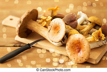 edible mushrooms on wooden cutting board and knife