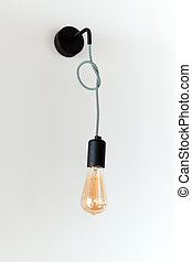 Edison retro lamp. Incandescent bulb on white wall background in loft. Concept of vintage style