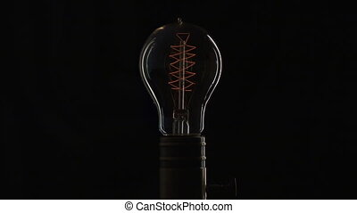 Edison's light bulb illuminates slowly from electric...