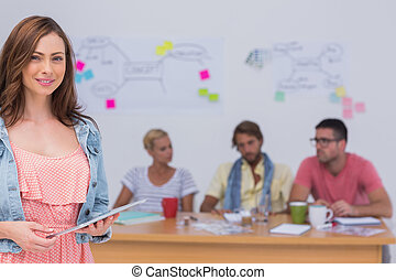 Smiling editor holding tablet as creative team works behind her at desk