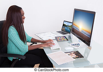 Editor Using Digital Tablet At Photo Agency