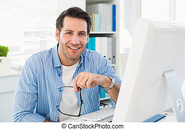 Editor working at his computer while looking at camera