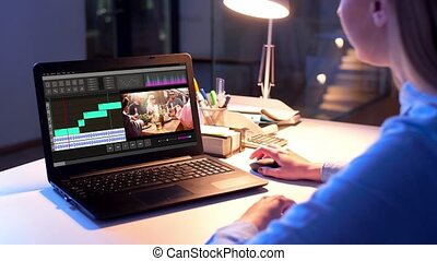 editor working on video file on laptop at night - post...