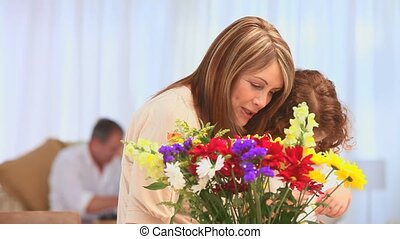 Edlerly woman with her grand daughter making a bunch of flowers