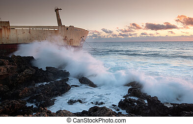 Abandoned ship resting on the rocks of the coastline of Paphos city in Cyprus.