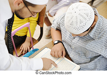 Education activities in classroom at school, Muslim teacher showing Koran to kid