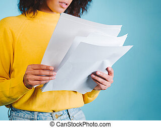 Education and business concept - international student studying in college. Or modern african american businesswoman with afro hairstyle reading documents on blue background in studio.