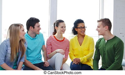 education and happiness concept - smiling students making high five gesture sitting on windowsill at school