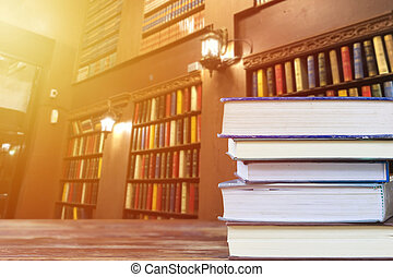 Education and reading concept: group of stack books on wooden table with colorful books on shelf in library as background and copy space. Back to school background with copy space for your text.