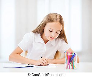 little student girl drawing at school - education and school...