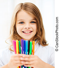 girl showing colorful felt-tip pens - education and school...