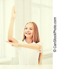 student girl with hand up at school