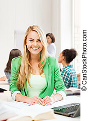 smiling student girl with laptop at school