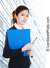 Young Business Women holding file standing in front building block.