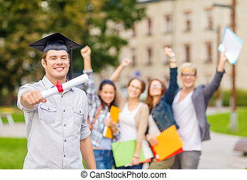 smiling teenage boy in corner-cap with diploma
