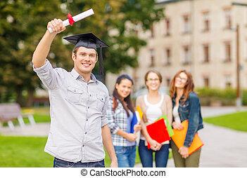 smiling teenage boy in corner-cap with diploma - education, ...